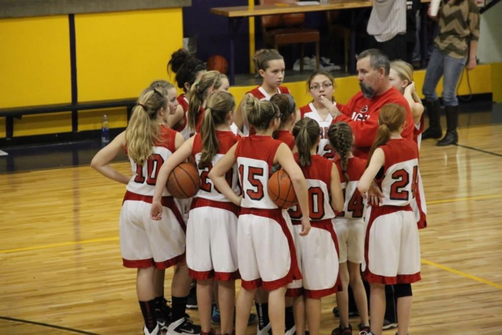 The Junior High girls basketball team huddles up to hear the game plan from Coach Tony Dodson. The girls had already won the night before and had high hopes of a winning streak. The girls went on to lose this game by 18-27 against Higgins , but took fourth overall in the tournament.