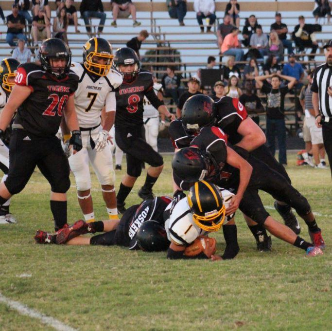 Three Tigers team up to make the tackle. One of these competitors, senior Nate Roskens, led the team with eight tackles. Juniors Mason Miller and Carson Ritter also were major factors for the Tigers' defense.