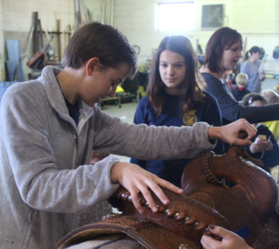 Katelyn Burger shows students the proper way to mount a horse on Feb. 26 at the AG Fair in the GHS AG shop. She and other eight-graders Hallie Thompson and Justina Cornado used a booth with a diagram combined with a real saddle to teach elementary through high school students the proper names for all the pieces of a saddle and the right way to get on a horse.
