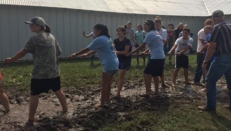 While participating at camp, freshman Hallie Thompson, in black in the middle, plays mud tug-of-war with her team. This is one of the many games to play after lunch.