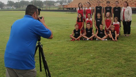 Photographer Chris DeLeon with Lifetouch shoots the junior high cross country team as sprinkles begin to fall. The rain held off long enough for all pictures to be done before lunch.