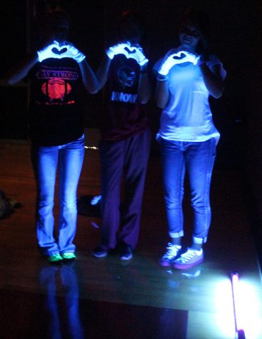 Cheerleaders test black-out lights and form hearts to show their love for the Tigers. The black light pep rally always takes place on one Oct. Friday.