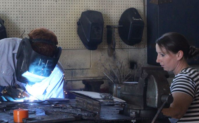 Jennifer Carter supervises as her welding students finish projects. Carter is exactly 4-foot-11, and she often blends in with the students. Some say she's the woman who brings light to the halls of Groom, not only because her favorite color is yellow, but for her bright and bubbly personality.