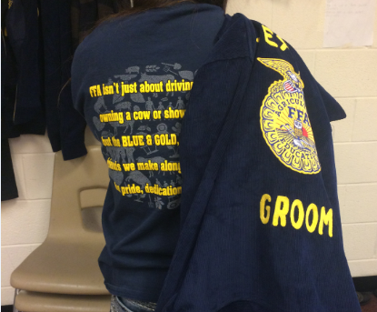 Freshman Justina Coronado holds a Groom FFA jacket over her shoulder as a reminder of tonight's dinner before the bond meeting. As well as a dinner before the meeting, there will also be a raffle of various items.