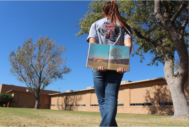 Sophomore Sydney Ritter stands in front of the school holding a yearbook from 1966. The very first page of the yearbook is a picture of the face of the school.