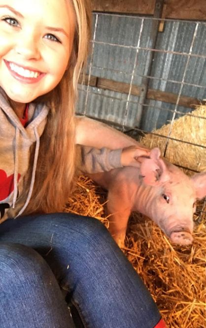 Sophomore Halle Barkley poses with her pig, Strawberry. Barkley will take this pig to the Carson County Junior Livestock Show, as well as the San Antonio or Houston show.