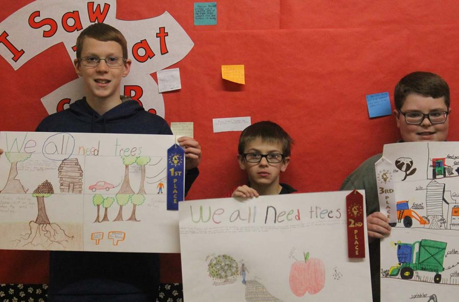 Fifth-graders Ryan Weinheimer, Jacob Ragain and Gage Whatley show off their award-winning artwork today outside of Mrs. Dana Britten's class. The McClellan Creek Soil and Water Conservation Board sponsored the contest. Weinheimer took first place; Ragain placed second, and Whatley earned  the third spot.