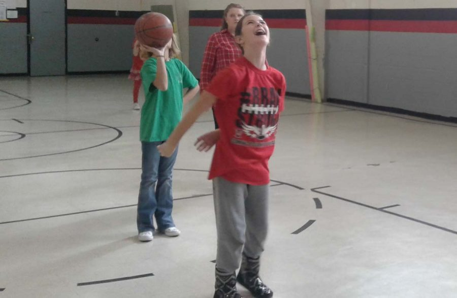 Fifth-grader Alexis Ritter does her form shooting in P.E. in her red shirt.Students were asked to wear Red to show their support for the Tigers and Tigerettes, who play Shamrock tonight, Jan. 10 starting at 6. I think that if we work together, we can overcome any obstacle that we face, junior Morgan Trevino said.
