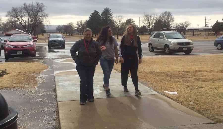 Junior girls Morgan Trevino, Jamey Germany and Chelsey Lamb walk into the school from lunch on the wet, snow-melted sidewalks. Students had a two-hour delay this morning due to icy conditions.