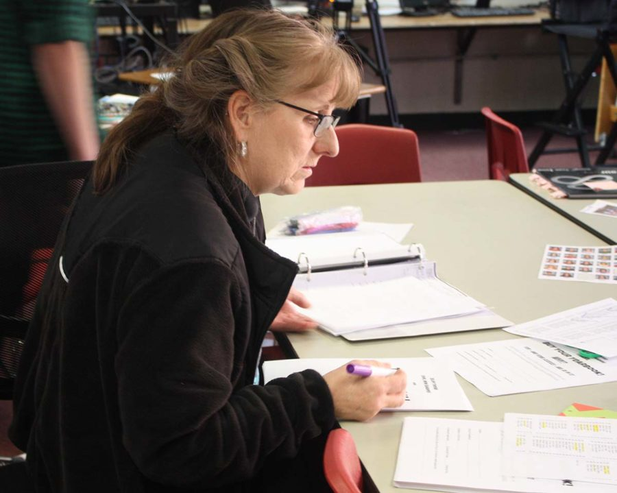 Journalism adviser Lisa Roskens prepares yearbook order forms to be sent home with students today, Feb. 27. Spring picture day took place this morning, and all students were included in the all-school photo with their own pair of sunglasses.