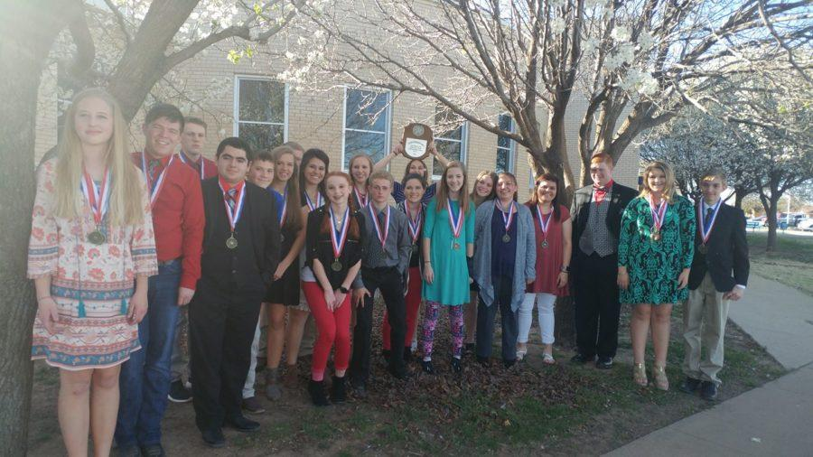 20 OAP cast and crew members gather around their advancing play plaque. The group earned numerous of awards at District and will be advancing to bi-district, which will be on Thursday, March 23 in Fort Elliott. It was nerve-wracking waiting to see if we would get called, freshman Ginna Miller said.