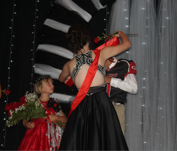 Senior Caroline Britten puts the homecoming  sash on senior Carson Ritter. The coronation is one of the long-kept traditions of Groom High School.