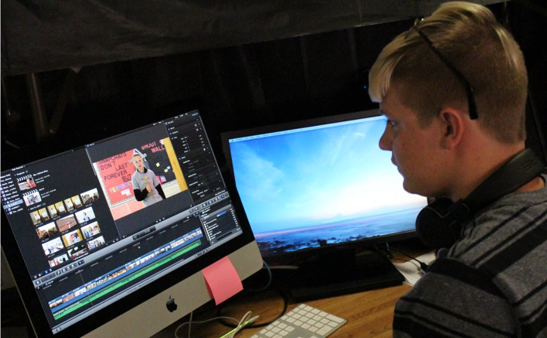 Photo Editor Kodi Tiffin lends a helping hand to the Spanish II class in editing film for their video. The group had an assignment to create a video for the phrase