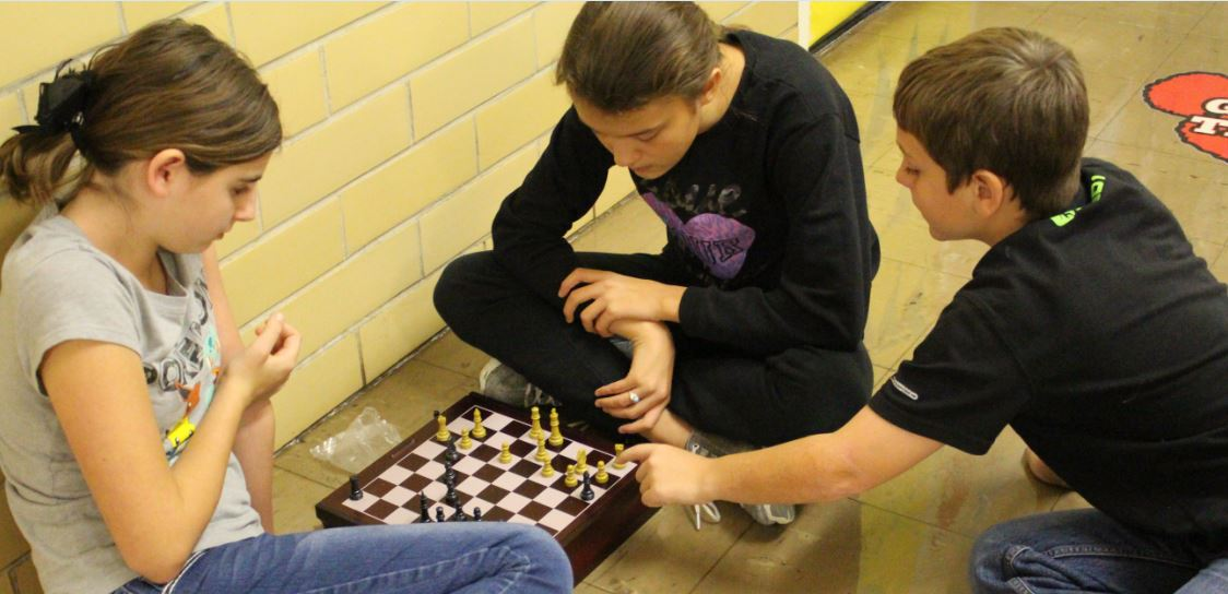 Fifth-grader Trayson Corley, right,  assists sixth-graders Kye Mays and Brandi Tipton as they play a game of chess during the CLAWS activity period. The students are practicing their UIL events for the official meet on Dec. 18.