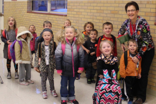 Pre-K teacher Pam Hutsell takes time for a quick photo with her preschool students before lining up to go to class. Hutsell left retirement to rejoin the Groom faculty this school year.
