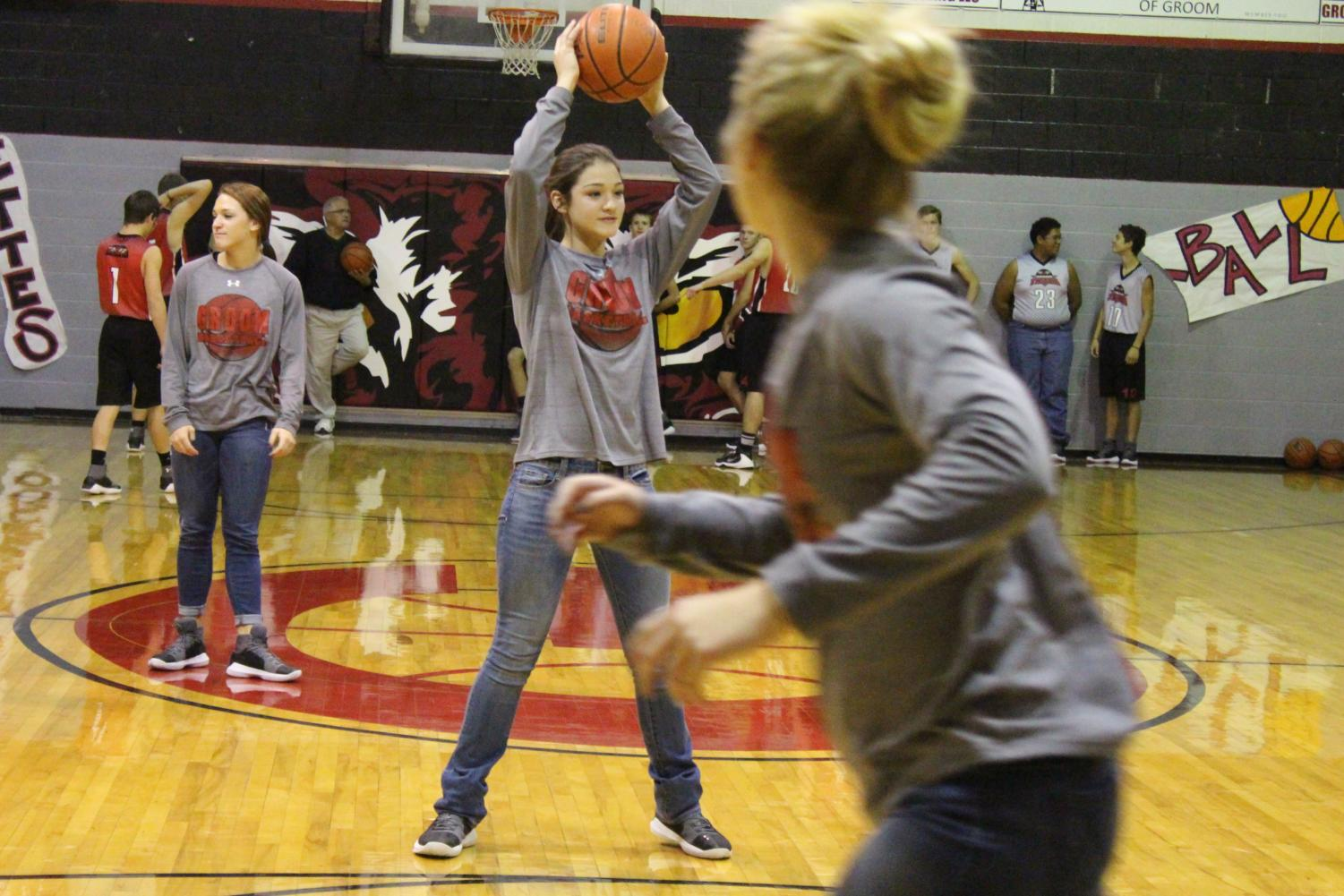 Varsity basketball team member and freshman Aubrey Ritter searches for an open teammate to pass the ball during a drill. Groom's girls' and boys' basketball teams will be playing tonight at 6 at Adrian's gym.