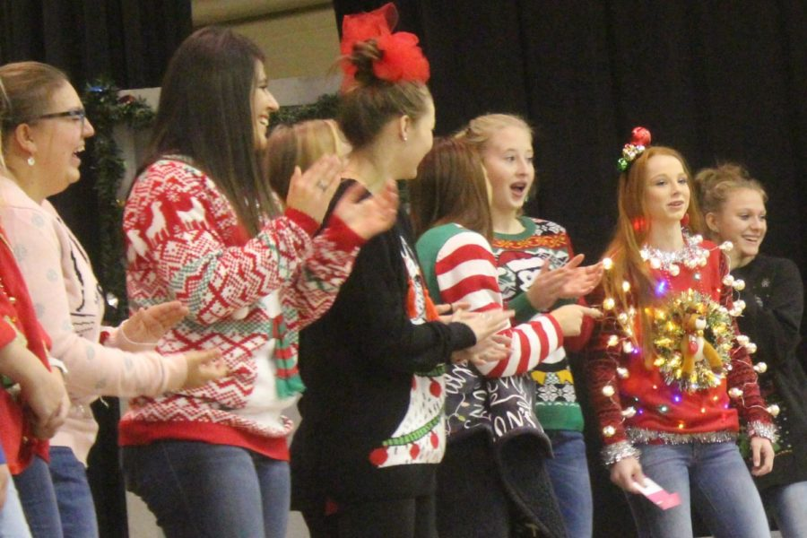 As the high school girls cheer her on, sophomore Ginna Miller, the winner of the high school ugly sweater contest,  returns back to the nominee line after voting. Other winners include kindergartner Lillian Barkley for the elementary. A sixth-grader, whose name cannot be mentioned online, took first for the junior high division. Melanie Britten took the faculty prize. It  was fun to compete even though I had no chance, eighth-grader Saffron Eugea said.
