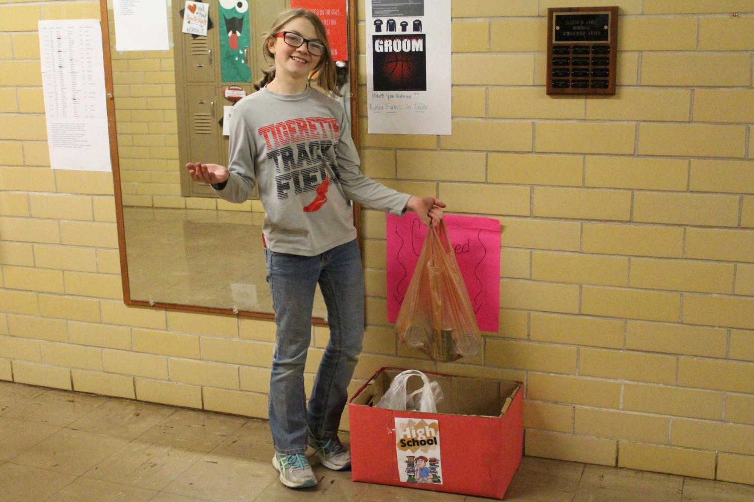 Eighth-grader Sam Short donates a bag of goodies to the canned-food drive. This event, which is being headed by the student council and the National Honor Society, will end Dec. 20. Then, on Dec. 21 the groups will hold a canned-food sculpture contest, and the winner gets a pizza party. All collections will go to the Groom Helping Hands Food Pantry.