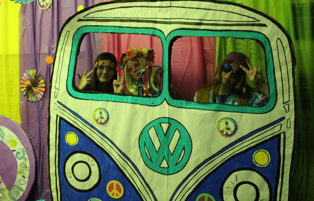 Juniors Justina Coronado, Ginna Miller and senior Reganne Boyd pose in the set up hippie bus made by the cheerleaders for the 60's day themed homecoming day. This one of many dress up days during this week. Tomorrow is Disco day for the 70's.