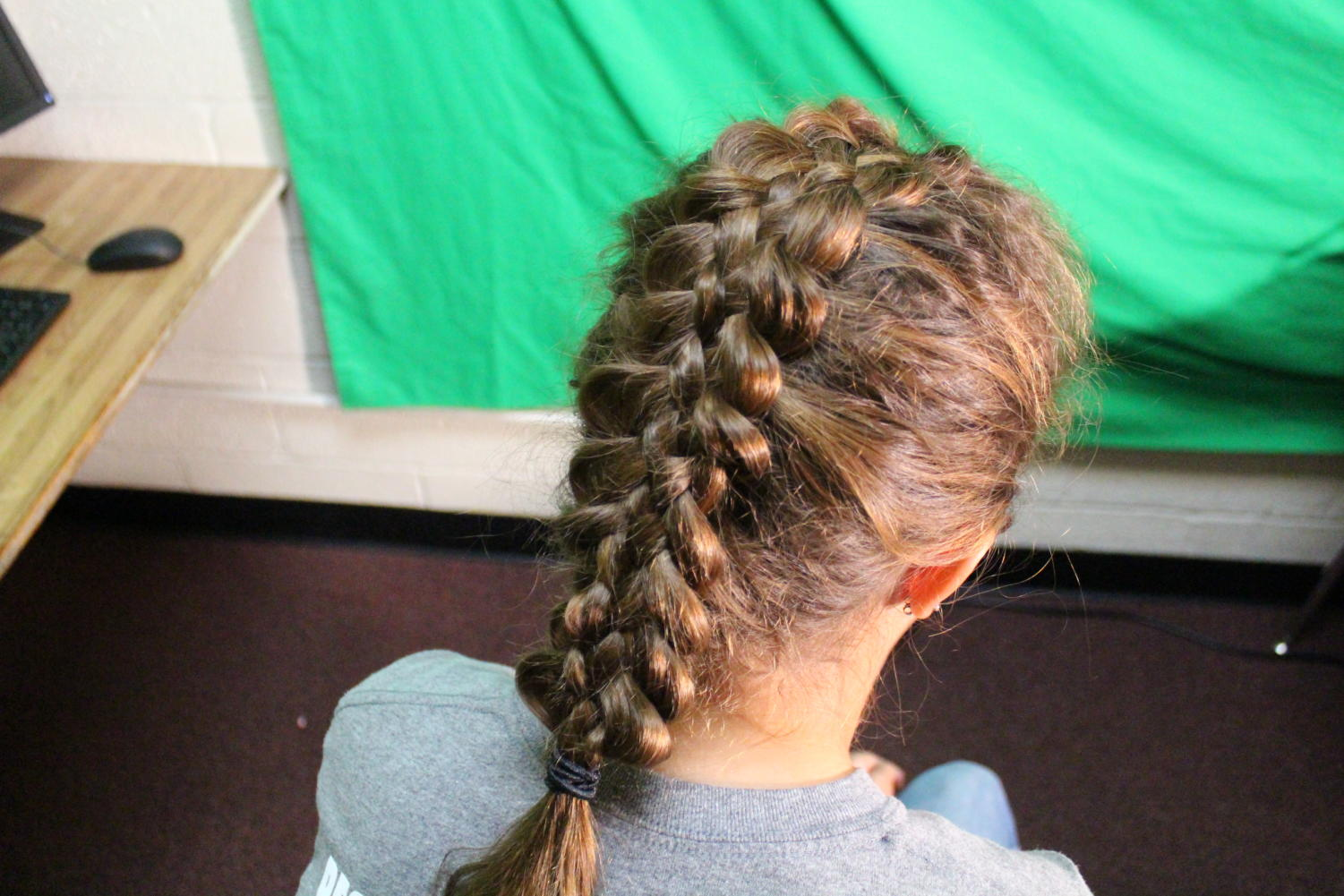 Eighth grader Brandi Tipton is used as a model for Staff Writer Saffron Eugea. Tipton is modeling the five strand braid.