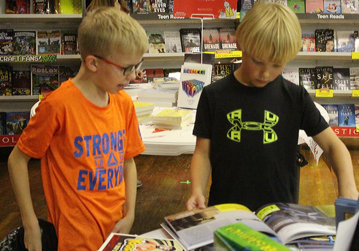 Fourth graders Jake Babcock and Brock Britten search among the broad selections of books. The book fair will be open from 8 a.m. to 4 p.m. if you put some books aside, you have till Friday to pay them which is the last day the fair will be open.