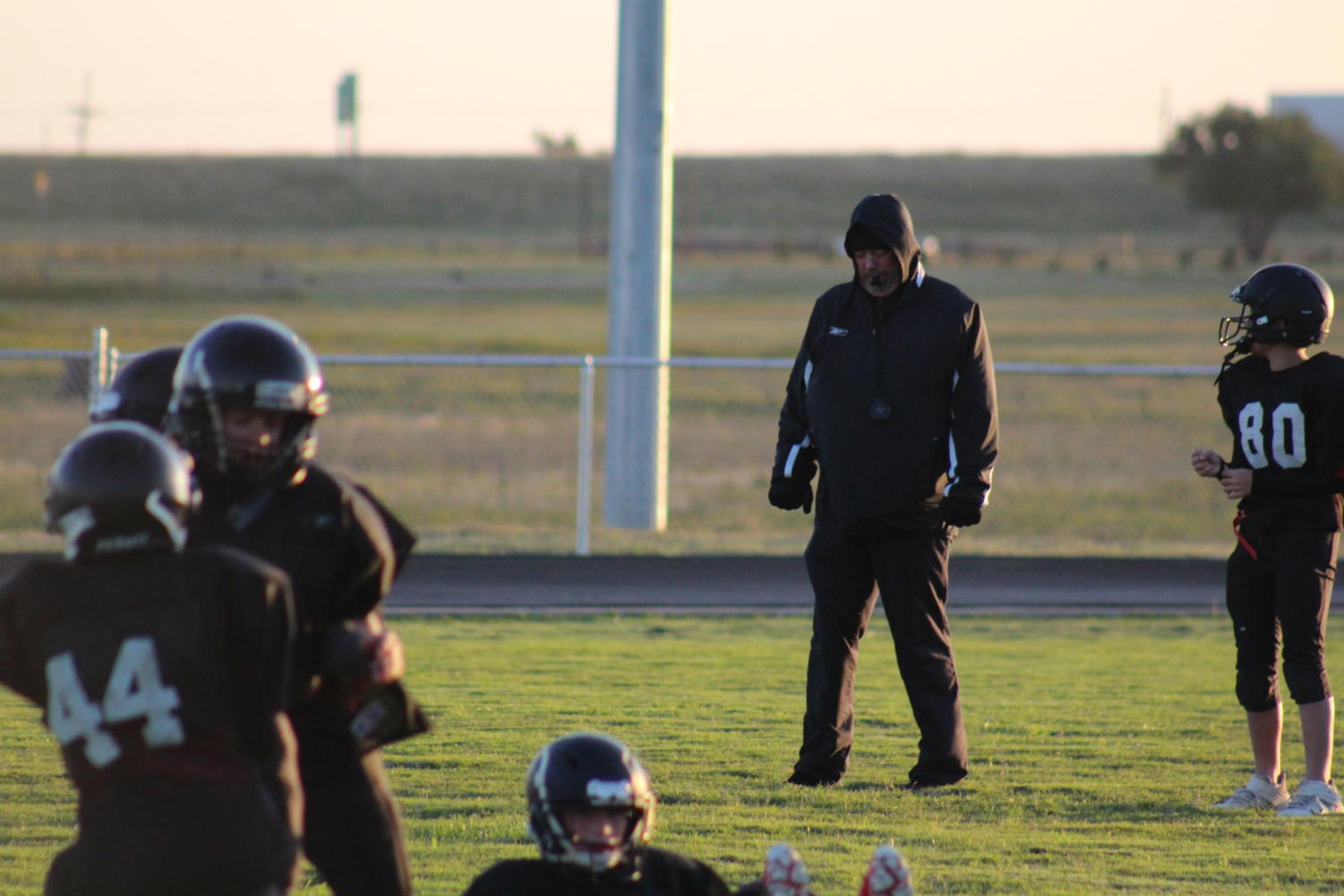 Looking like Darth Vader, Coach Peet stays warm for outdoor training,