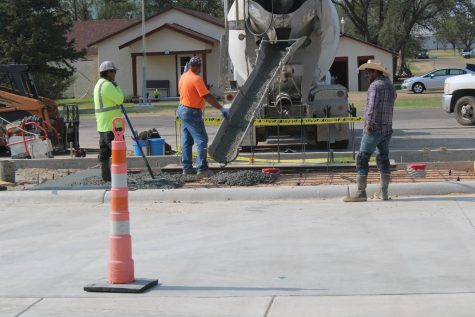 Senior Graci Treadwell snaps a photo of the last pour. The front concrete is officially over and done.