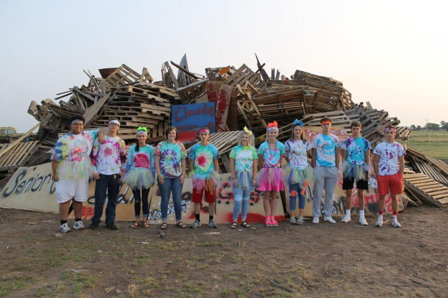 The Senior class stands around the Bonfire for a photo dressed in all their Tye-Dye.